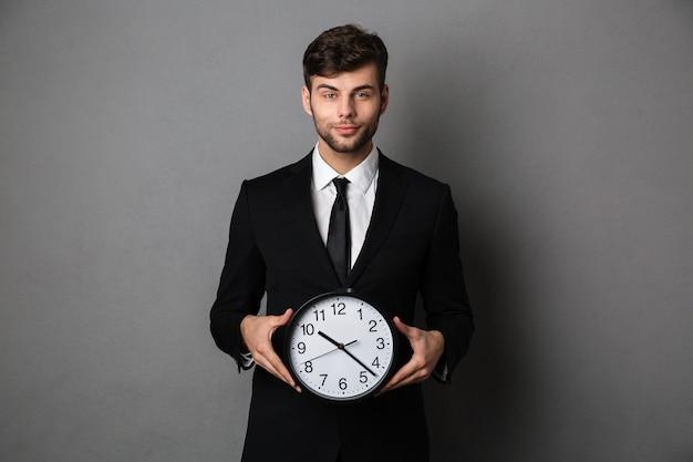 Jonge vrolijke zakenman die in zwart kostuum grote klok houdt,