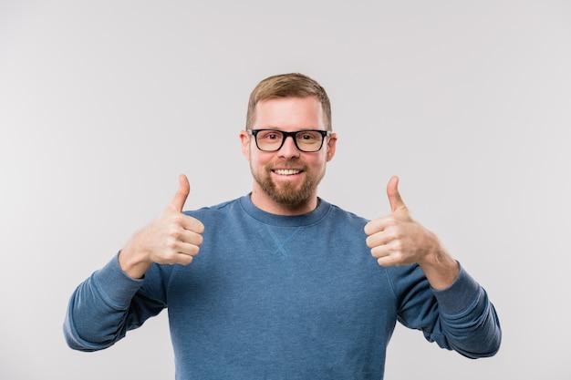 Jonge vrolijke zakenman in blauwe pullover duimen opdagen terwijl hij geïsoleerd voor de camera staat