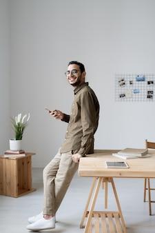 Jonge vrolijke zakenman met behulp van smartphone terwijl staande door tafel voor camera in kantoor