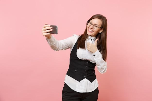 Jonge vrolijke zakenvrouw in pak, bril doet selfie schot op mobiele telefoon met duim omhoog geïsoleerd op roze achtergrond. dame baas. prestatie carrière rijkdom. kopieer ruimte voor advertentie.