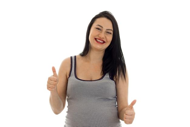Jonge vrolijke zwangere moeder duimen opdagen geïsoleerd op een witte achtergrond in studio