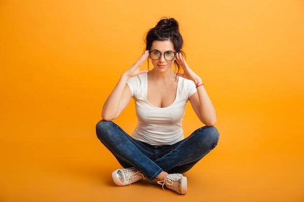 Jonge vrouw 20s in casual kleding en brillen poseren op camera met schattige look zittend met benen gekruist op de vloer, over gele muur