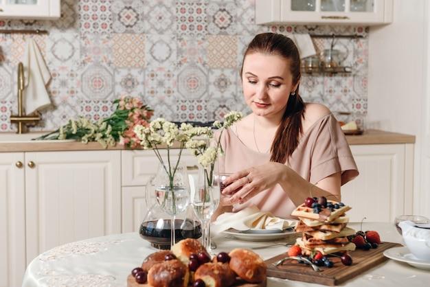 Jonge vrouw aan de tafel met gekookt ontbijt.
