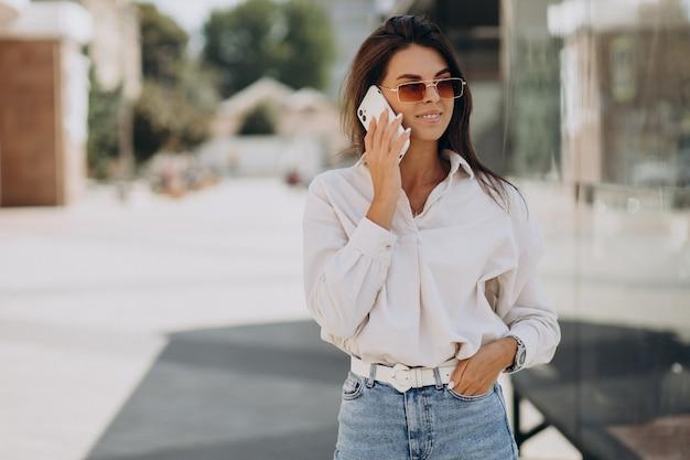 Jonge vrouw aan de telefoon buiten de straat