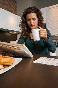 Jonge vrouw aan het ontbijt in de keuken en op zoek naar de krant