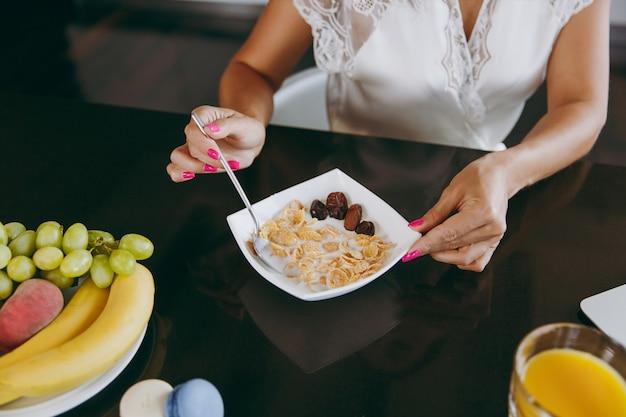 Jonge vrouw aan het ontbijt met granen en melk and