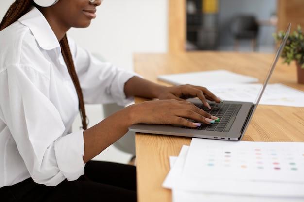 Jonge vrouw aan het werk met haar koptelefoon op
