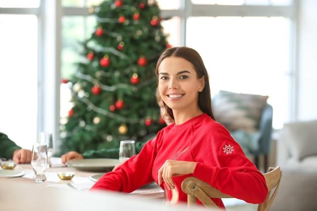 Jonge vrouw aan tafel op kerstavond