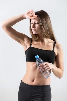 Jonge vrouw aan te raken haar voorhoofd na de fysieke activiteit