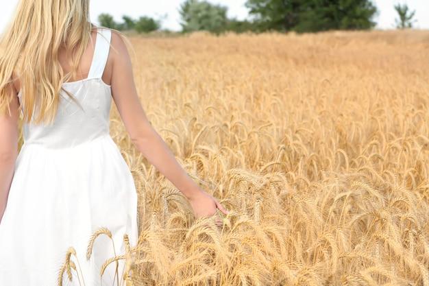 Jonge vrouw aanraken van tarwe in veld