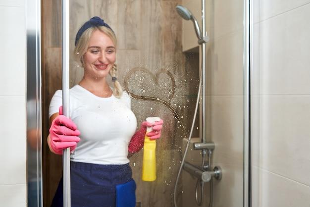 Jonge vrouw achter doucheglas met hart dat erop trekt