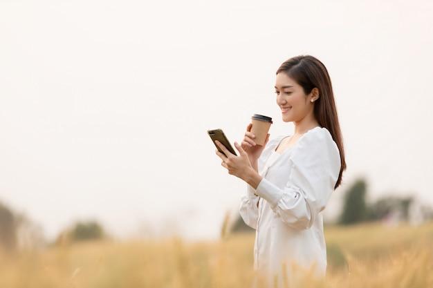 Jonge vrouw afhaalmaaltijden koffiekopje staande buitenshuis met smartphone op gerst veld land in de ochtend te houden. gelukkige tijd.