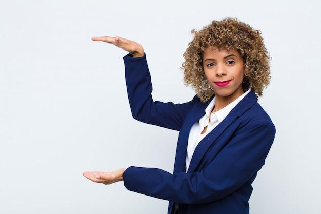 Jonge vrouw afrikaanse amerikaan die een voorwerp met beide handen op zijexemplaarruimte houdt, een voorwerp op vlakke muur toont, aanbiedt of adverteren