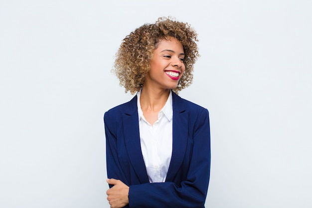 Jonge vrouw afrikaanse amerikaan die gelukkig, vrolijk en zeker kijkt, trots glimlacht en aan kant met beide handen op heupen tegen vlakke muur kijkt