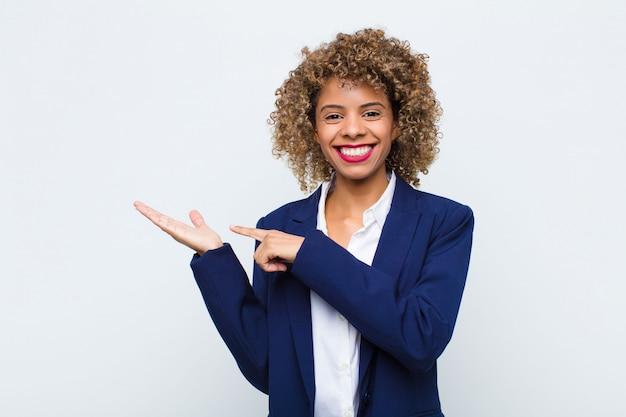 Jonge vrouw afrikaanse amerikaan die vrolijk glimlachen en ruimte op palm aan de kant richten kopiëren, of een voorwerp tegen vlakke muur tonen of adverteren