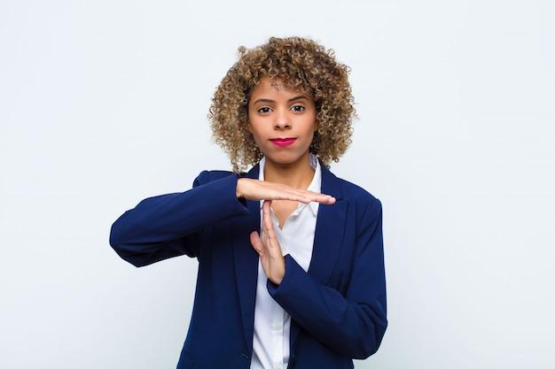 Jonge vrouw afro-amerikaan die ernstig, streng, boos en ontevreden kijkt, time-outteken maakt tegen vlakke muur