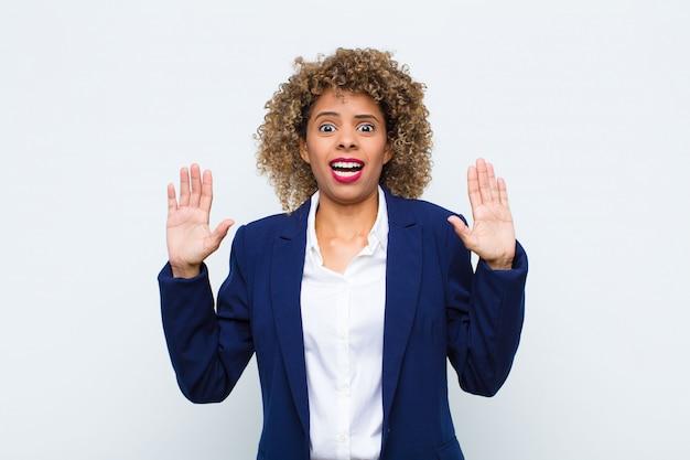 Jonge vrouw afro-amerikaan die zich stomverbaasd en bang voelt, bang is voor iets beangstigend, met de handen open vooraan en zegt: blijf weg op een vlakke muur
