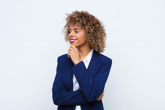 Jonge vrouw afro-amerikaanse lachend met een gelukkige, zelfverzekerde uitdrukking met de hand op de kin, zich afvragend en kijkend naar de zijkant op een vlakke muur