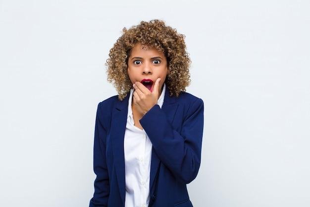 Jonge vrouw afro-amerikaanse met mond en ogen wijd open en hand op kin, onaangenaam geschokt voelen, zeggen wat of wauw op vlakke muur