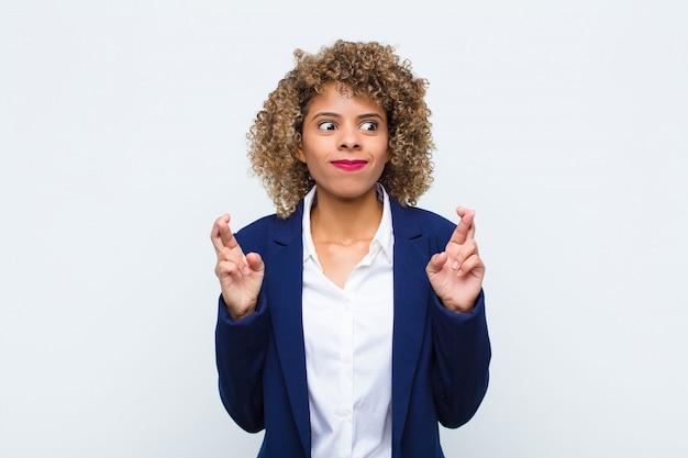 Jonge vrouw afro-amerikaanse vingers angstig kruisen en hopen op geluk met een bezorgde blik op de vlakke muur