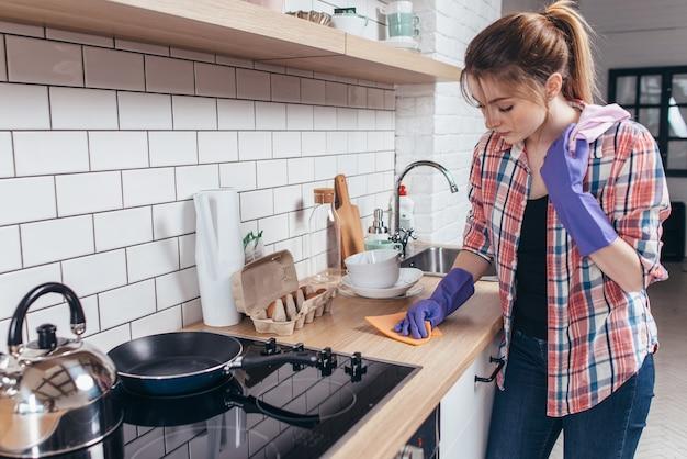 Jonge vrouw afvegen tafel in de keuken.