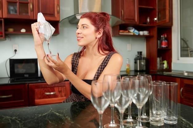 Jonge vrouw afvegende wijnglazen