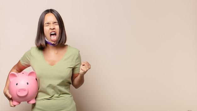 Jonge vrouw agressief schreeuwen met een boze uitdrukking of met gebalde vuisten het vieren van succes