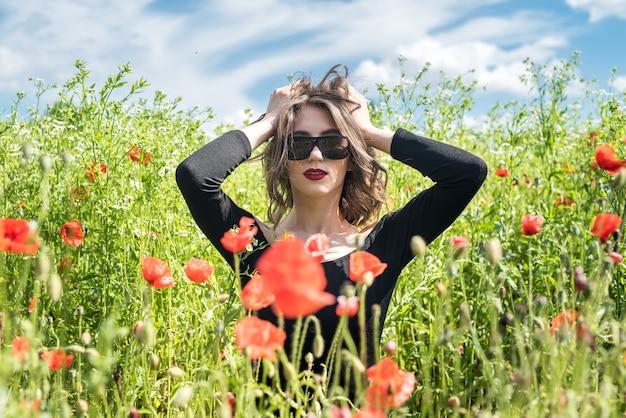 Jonge vrouw alleen bij papaver in veld zomerdag, lifestyle
