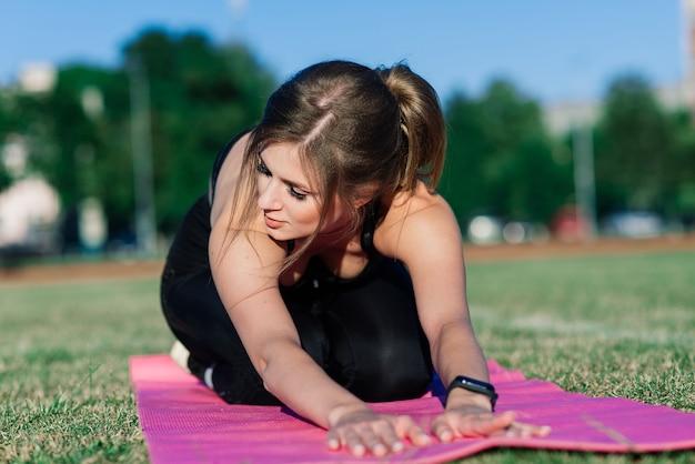 Jonge vrouw alleen in het stadion doet yoga