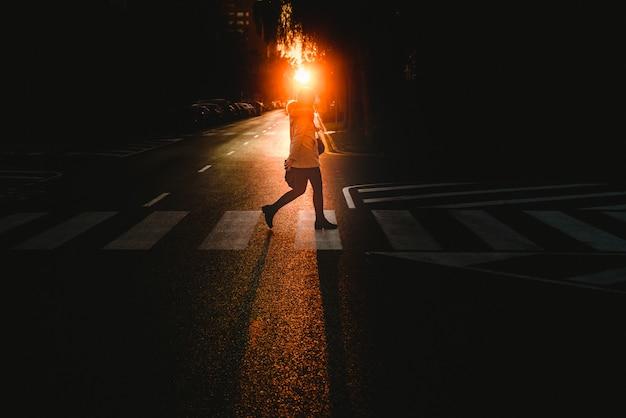 Jonge vrouw alleen lopend en kruisend een eenzame straat door een voetgangersoversteekplaats bij zonsondergang