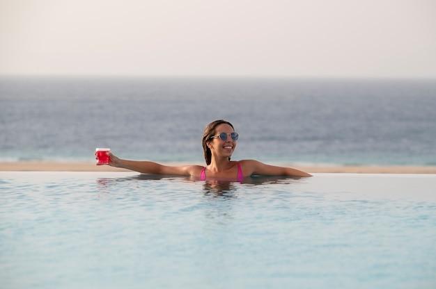 Jonge vrouw alleen ontspannen in het zwembad