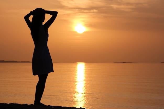 Jonge vrouw alleen ontspannen op de oceaan zand kust aan zee genieten van warme tropische avond.