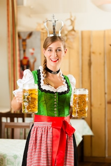 Jonge vrouw als koningin in traditionele beierse klederdracht in restaurant