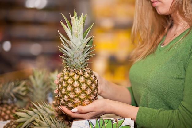 Jonge vrouw ananas kopen in een supermarkt.