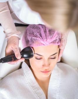Jonge vrouw apparatuur behandeling in cosmetologie kliniek ontvangen. cosmetologie huidverzorging. esthetische gezichtsbehandeling concept.