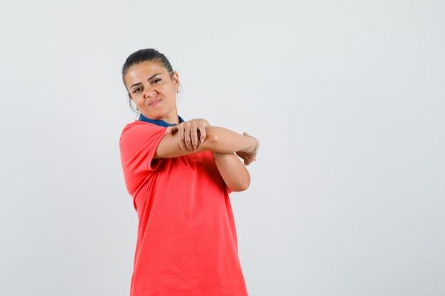 Jonge vrouw armen in rood t-shirt uitrekken en moe op zoek. vooraanzicht.