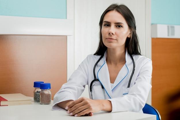 Jonge vrouw arts aan tafel