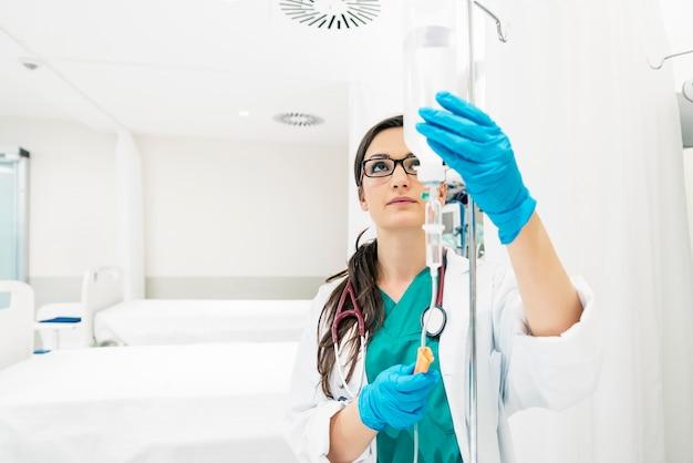 Jonge vrouw arts anesthesioloog gekleed in groene jurk, zet de druppelaar