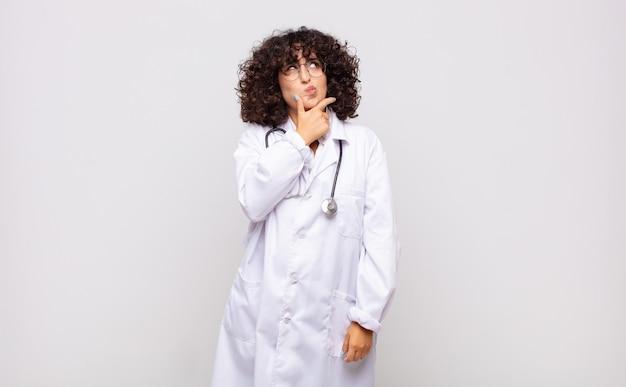 Jonge vrouw arts denken, twijfelachtig en verward voelen, met verschillende opties, zich afvragend welke beslissing te nemen