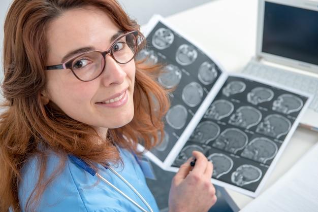 Jonge vrouw arts die een röntgenstraal in een bureau bekijkt