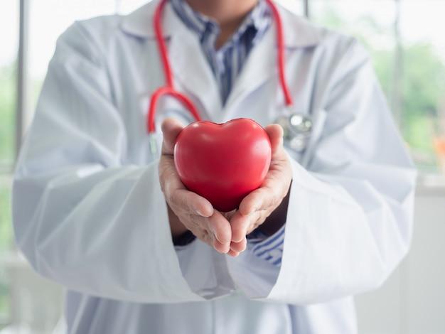 Jonge vrouw arts die een rood hart in laboratorium houdt