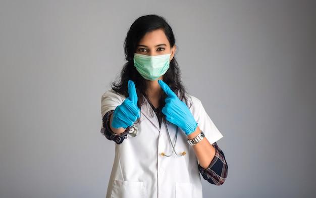 Jonge vrouw arts die medisch gezichtsmasker draagt dat teken toont. artsenvrouw die chirurgisch masker voor coronavirus dragen.