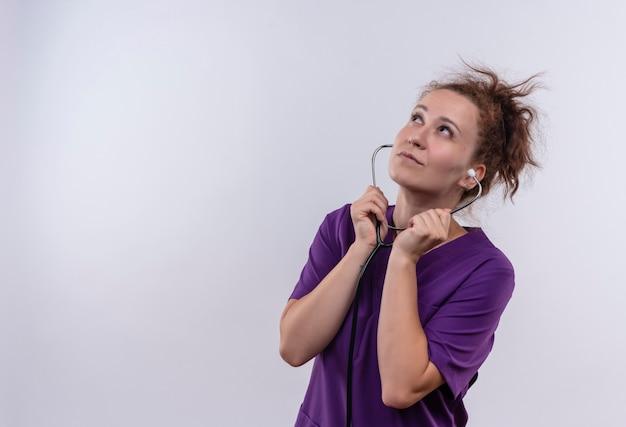 Jonge vrouw arts die medische eenvormige listetning met stethoscoop draagt die omhoog verward status over witte muur kijkt