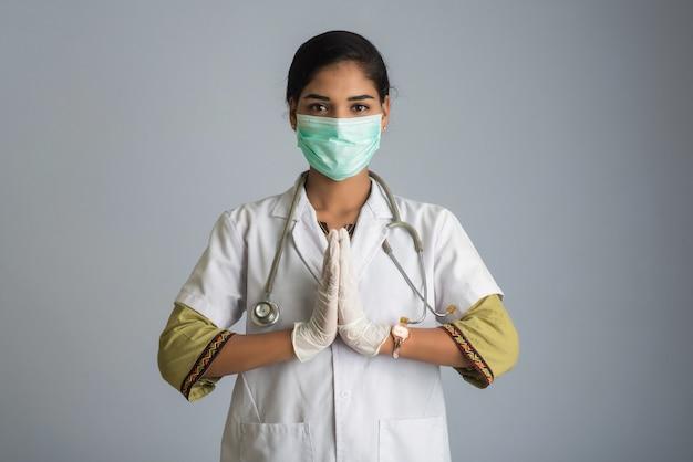 Jonge vrouw arts die namaste doet wegens het uitbreken van covid-19. nieuwe begroeting om de verspreiding van coronavirus te voorkomen in plaats van te begroeten met een knuffel of handdruk.