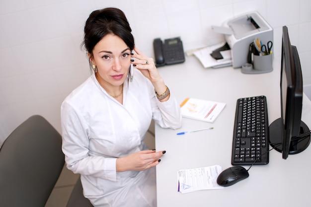 Jonge vrouw arts die telefonisch spreekt en iets in haar bureau schrijft