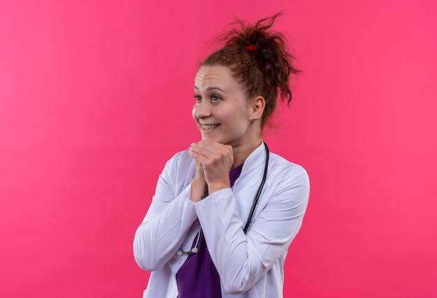 Jonge vrouw arts draagt ?? witte jas met stethoscoop hand in hand samen op zoek verrast staande over roze muur