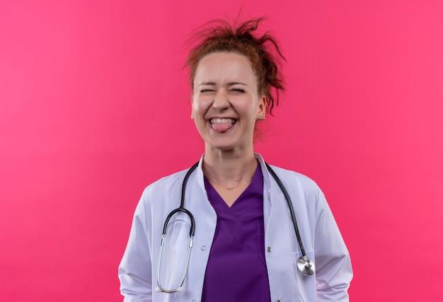 Jonge vrouw arts dragen witte jas met stethoscoop blij en verlaten tong uitsteekt staande over roze muur