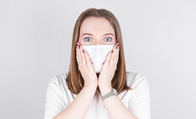 Jonge vrouw arts in een medisch masker kijkt met verbazing naar de camera en houdt haar gezicht met haar handen vast. ð¡ concept van covid 19, griep en seizoensgebonden verkoudheid.
