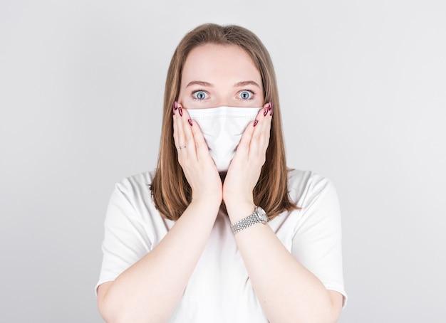 Jonge vrouw arts in een medisch masker kijkt naar de camera