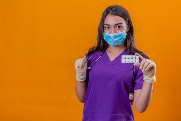 Jonge vrouw arts in medisch uniform met phonendoscope die beschermend masker draagt en handschoenen die holdingsblaar met pillen en opgeheven vuist over geïsoleerde oranje achtergrond glimlachen
